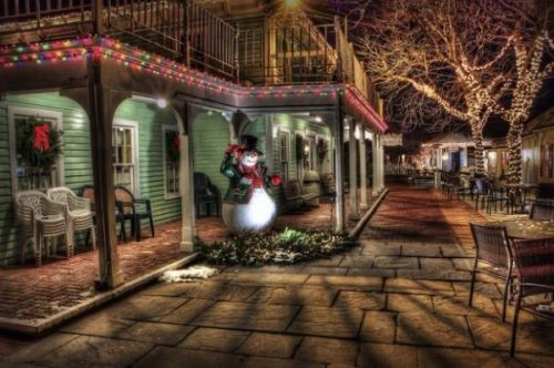 Featured Image Of A Christmas Snowman Outside A Well Lit House Porch/Verandah.