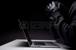 23730970-computer-hacker-in-a-balaclava-working-in-the-darkness-stealing-data-and-personal-identity-informati
