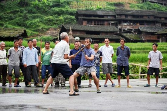 "Pic shows: Some people practicing Kung Fu. Locals in this village have every reason to be proud of their martial arts skills, after all not only have they been practising for three centuries they even have a martial arts discipline named after them. And far from being a dying art, it's now so popular in Gundi village in Tianzhu County, in south-west China's Guizhou Province, that even the women and the children join in as well as the men. Despite its official name the village is better known as ""kung fu village"", as all of its residents have a habit of regularly practicing martial arts in the mornings and evenings. The 123 households comprise Dong people, one of China's many ethnic minorities, who have been living in the region for hundreds of years. The Dong even developed their own fighting technique known as the Black Tiger style, or ""Heihuquan"" in Chinese, which is characterised by its extensive footwork, acrobatic kicks, low, wide stance, and unique fist positioning. The fighting style also has a history of 300 years and has been kept alive with the regular practice sessions. As for the reason behind the popularity of kung fu in the village, locals claimed its roots lie in their ancestors need to defend themselves and their livestock from predators and bandits descending from the surrounding mountains. Others said it was because the Dong people were often discriminated against in the past and felt the need to stand up for themselves. In the past, only men practiced martial arts, but now women have also joined in. The tradition is also handed down from generation to generation. The villagers say they now practice the Black Tiger style for health reasons, although they also point out that it could still be useful if they ever have to fight off any ill-intentioned visitors.photocredit/thanks:cen"
