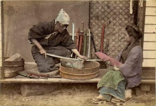 Featured Image Of An Olden Japanese Samurai/Blacksmith Cleaning Weapons with A Female Assistant.