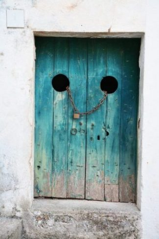 Image Of An Old Faded Blue Chain Locked Wooden Door In A White Doorway Arch.