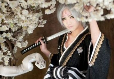 Image Of A Japanese Woman In Kimono Carrying A Sword Whilst Nearby In White Flowery Vines Is A White Snake.