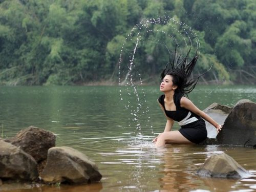 Featured Image Of A Young Lady In A Lake With An Arc Of Water Splashed From Her Hair.