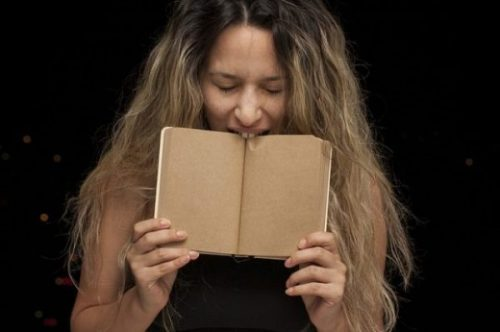 Featured Image Of A Young Women Biting Down On A Book.