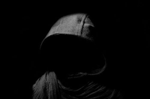 Featured Image An Unseen Person In A Hooded Cloak.
