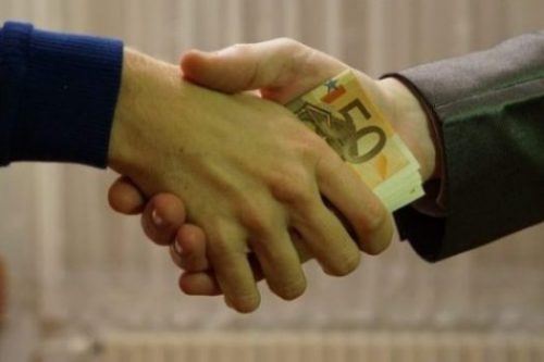 Image Of Two Business Mens Hands Shaking With Money Pressed In 'Tween.