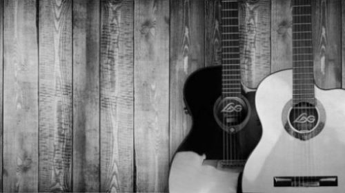 Featured Image Of A Black And White Guitar Leaning Against A Wood Fence.