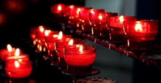 Several Small Diagonal Rows Of Red Candle Glasses All Alight In Darkened Room.