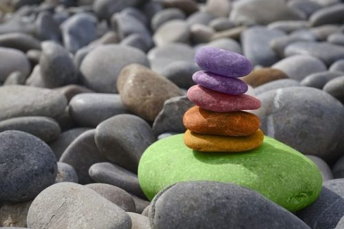 Image Of Beach Stones With Several Colored Arranged In A Zen Type Pile.