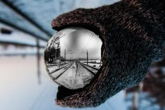 Snow Bound Scene Reflected In A Crystal Ball Held In A Glove.