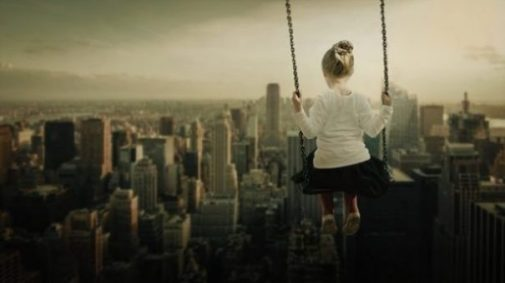 Featured Image Of A Young Girl On A Swing Overlooking Suburbia.
