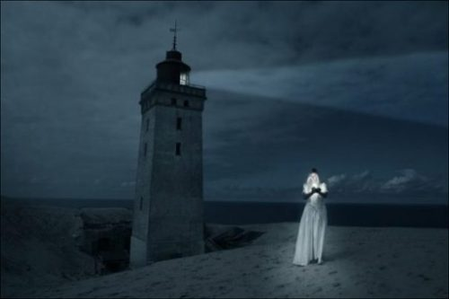 Featured Image Of A Night Lit Lighthouse With A Woman Holding A Light Walking Nearbys.