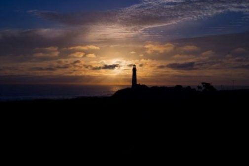 Featured Image Of An Unlit Shadowed Lighthouse At Sunset.