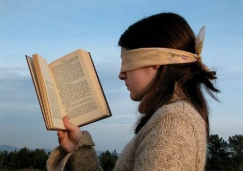 A Blindfolded Young Woman Reading A Book.