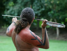 Image From Behind Of An Australian Aboriginal Warrior Holding A Woomera And Spear Ready To Throw.