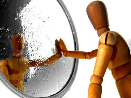 Wood Toy Puppet Figure Looking In A Mirror.