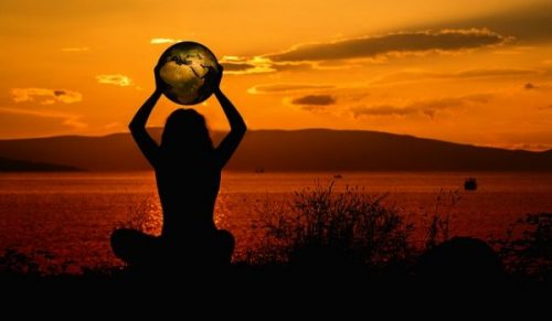 Shadowed Figure Holding Aloft A World Globe In The Sunset. Mountains, Waters And Sky In The Background.