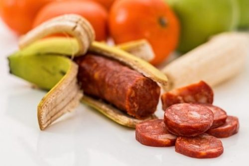 Image Of Several Fruits With A Banana Opened Revealing A Salami Inside.