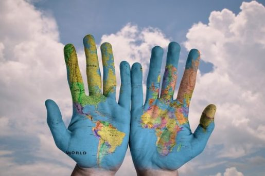 Image Of A Pair Of Open Hands Painted With A Colored World Map Backgrounded By Blue Sky, White Clouds.