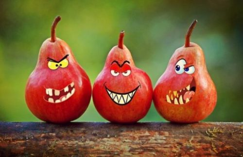 Featured Image Of A Trio Of Red Pears With Painted Sarcastic Grins.