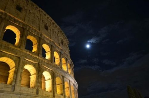 Image Of Romes Colisseum On A Clouded Moonlit Night With Most Of Moon Covered.