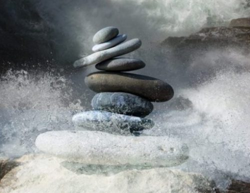 Featured Image Of A Pile Of Zen Stones Being Washed Away At The Beach.