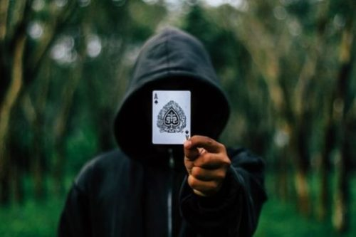 Featured Topic Image Hooded Magician Holding Up A Playing Card. The Card Is The Ace Of Spades. Out Of Focus Lined Trees In The Background.