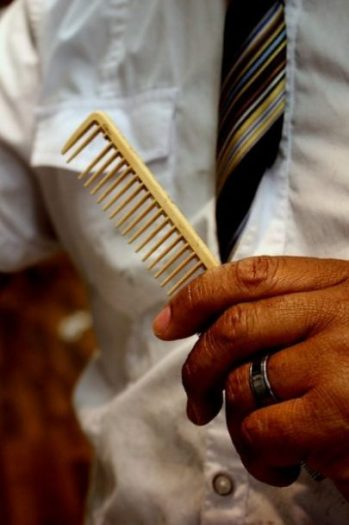 Featured Topic Image Man With White Shirt, Striped Tie Holds A Comb. Focus On Comb.