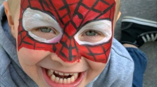 Child Wearing Superhero Spiderman Type Painted Face Mask.