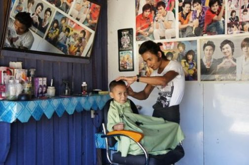 Featured Topic Image Seated In A Barbers Chair, A Young Boy Gets A Haircut. The Barber Works Away Surrounded By Pop Star Posters On The Walls. A Shelf Nearby Holds Equipment. The Young Boy Appears Slightly Apprehensive.