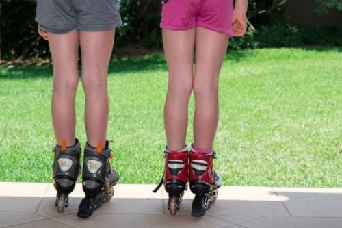 Pair Of Children Wearing Rollerskates Looking Over A Grassy Area.