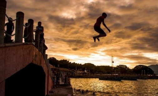 Young Adult Jumping Off Bridge/Jetty Into The Water Below. Background Sunset, Forest, Water Banks.