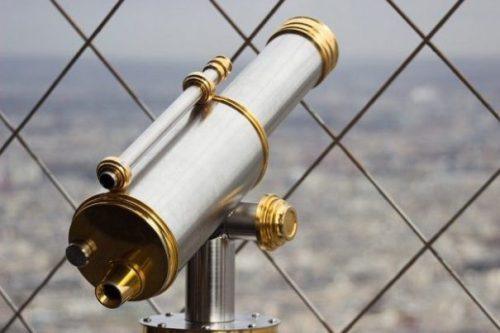 Featured Topic Image Telescope Pointing Upperly Through Mesh Fence. Out Of Focus City Background.