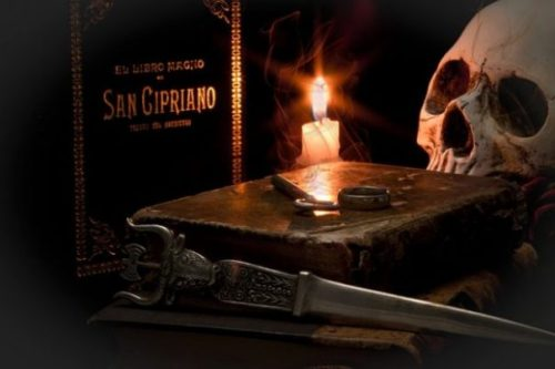 Featured Image Ancient Magic Ritual Scene. Grimoire, Skull, Candle, Ring, Key, Book and Knife Arranged Around Candle Lit Background. Ring And Key On Top Of Book.