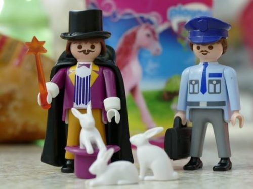 Featured Topic Image Wand Holding Cloaked Top-Hat Lego Magician With Rabbits Out Of A Hat. A Lego Police Officer and Pink Unicorn Toy Observes Nearby.