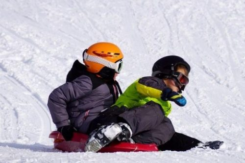 Featured Image Two Helmet Wearing and Goggled Children Snowboarding.