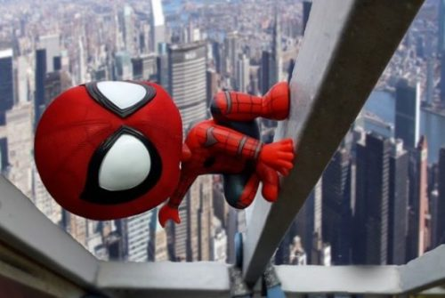 Featured Image Fantasy Toy Super Hero Spiderman Climbs Hi Rise Building In A City Day Scene.