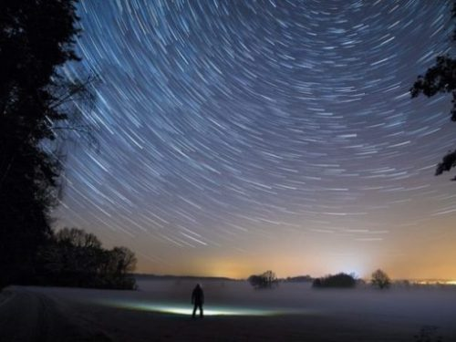 Featured Theme Image At Edge Of Forest Man In Lit Area Looks Skywards Whilst Stars Circle Overhead.