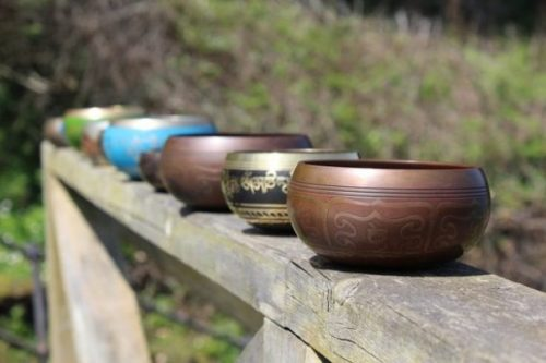 Featured Topic Image Row Of Singing Bowls Lined Up On A Fence/Gate.