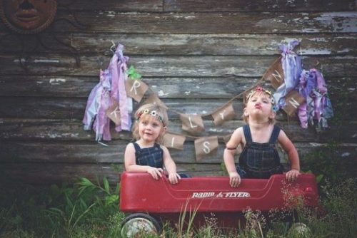 Featured Image Gemini Twin Children Sitting In A Toy Truck Playing Outside. A Colorful Banner Flies On The Wall.