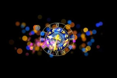 On A Black Background A Cluster Of Rainbow Lights Surround A Zodiac Timepiece/Device.