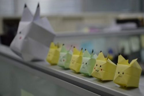 Set Of Yellow And Green Pikachu Type Origami Figures Lined Up On A Ledge.
