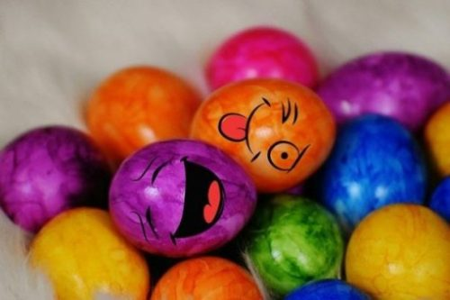 Featured Topic Image Lying Amidst Atop A Pile Of Other Many Colored Eggs, Two With Facial Features Smile, Smirk.