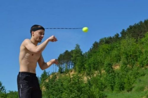 Featured Image Of A Bare Chested Man Plays Header Ball On Head Sling Toy. Forest Background.