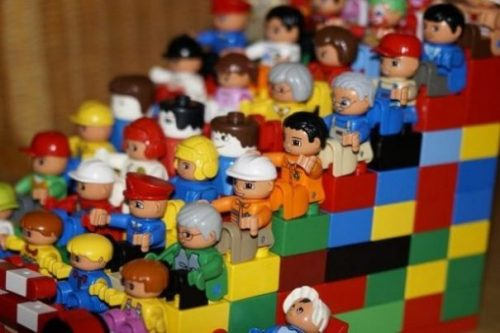 Rows Of Multi Colored Lego Figures On An Ascending Platform/Staircase.