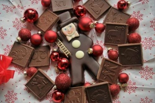 A Top Hatted Chocolate Man Is Surrounded By Chocolate Zodiac Squares and Red Christmas Icons.