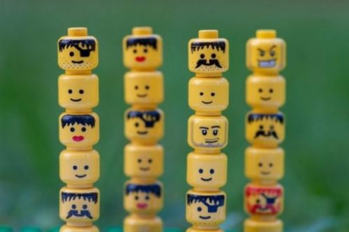 20+ Lego Figurine Heads Arranged Totem Style In A Row Of Four Stacks.