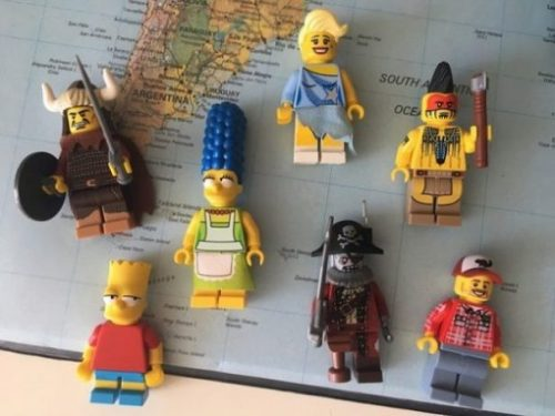 A Section Of The World Map With Several Hero/Cartoon Lego Figures Overlying.