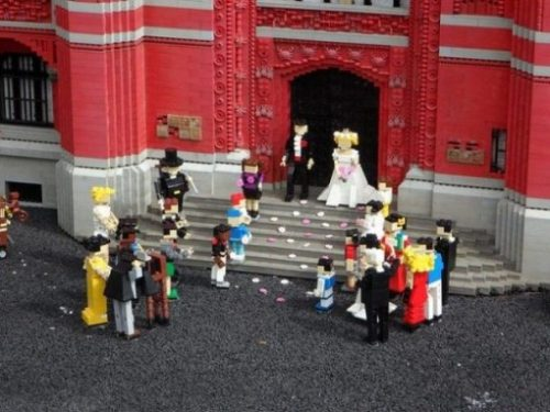 A Marriage Crowd Of Lego Figures Assembled Outside A Church. Bride And Groom On Stairs At The Entrance.