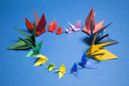 Set Of Colored Origami Figures Arranged In A Heart Shape On Blue Background.
